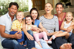 Två familjer som sitter utanför hus Fotografering för Bildbyråer