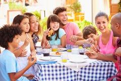 Två familjer som tillsammans äter mål på den utomhus- restaurangen fotografering för bildbyråer
