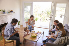 Två familjer som tillsammans hemma får royaltyfri bild