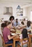 Två familjer som tycker om äta mål hemma tillsammans royaltyfria bilder