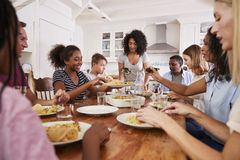 Två familjer som tycker om äta mål hemma tillsammans royaltyfria foton