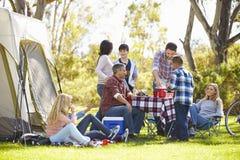 Två familjer som tycker om campa ferie i bygd arkivbilder