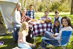 Två familjer som tycker om campa ferie i bygd royaltyfri bild