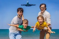 Två farsor och två söner har gyckel på stranden som håller ögonen på de landa nivåerna Resa på ett flygplan med ungebegrepp arkivbild