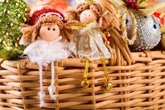 Två feer som sitter i en korg med julleksaker Arkivfoton