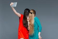 Två festliga kvinnor med framsidor som täckas av hår som tar selfie Royaltyfria Foton