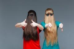 Två festliga kvinnor med framsidor som täckas av långt göra en gest för hår Arkivfoton