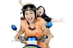 Två feta kvinnor som rider en moped på studio Arkivfoton