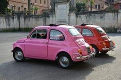 Två FIAT Cinquecento bilar målade med ljusa rosa färger och röda färger som parkerades i Rome Fotografering för Bildbyråer