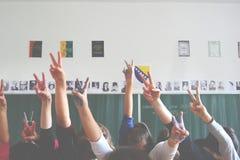 TVÅ FINGRAR: studenter i klassrumet royaltyfria bilder