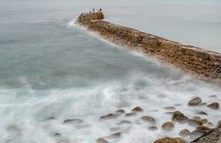 Två fiskare, Sennen vågbrytare, Sennen liten vik, Cornwall royaltyfri bild