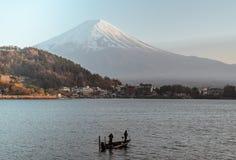 Två fiskare som fiskar på ett fartyg på sjön Kawaguchi med Mount Fuji royaltyfri bild