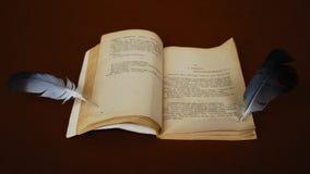 Två fjädrar och öppnar boken arkivbild