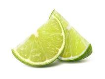 Två fjärdedellimefruktstycken som isoleras på vit Arkivbilder