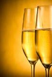 Två flöjter av champagne med guld- bubblor och utrymme för text Arkivbild