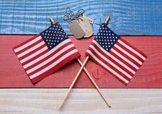 Två flaggor och hundetiketter på den patriotiska tabellen Arkivfoto