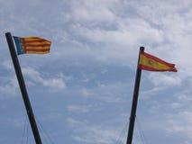 Två flaggor till vinden av Spanien och av Valencia spain Arkivbilder