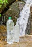 Två flaskor av dricksvatten på bakgrund av berget strömmar Fotografering för Bildbyråer
