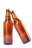Två flaskor av iskallt öl som isoleras på vit Royaltyfria Bilder