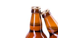 Två flaskor av iskallt öl som isoleras på vit Fotografering för Bildbyråer
