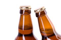 Två flaskor av iskallt öl som isoleras på vit Royaltyfria Foton