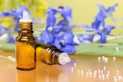 Två flaskor med homeopatismå kulor och blommor Arkivfoton