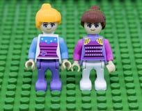 Två flicka Lego på grön bakgrund Arkivfoton