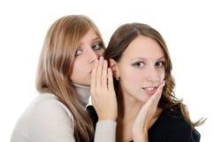 Två flicka-vänner berättar skvallrar på ett öra arkivbild