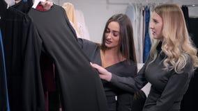 Två flicka-vänner på shopping går på shoppingmitt med påsar och väljaklänningen lager videofilmer