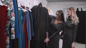 Två flicka-vänner på shopping går på shoppingmitt med påsar och väljaklänningen arkivfilmer