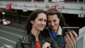 Två flickabästa vän som tar selfie och att stå på stadsbron och att tala och att le och att skratta Långsam mo arkivfilmer