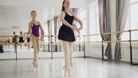 Två flickabalettdansörer öva att dansa på tåspetsarna med deras erfarna lärare under balettkurs i studio stock video