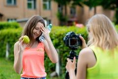 Två flickaskolflickaflickvänner Sommar i natur äta för begrepp som är sunt Handen rymmer flaskvatten och gräsplan Royaltyfri Foto