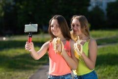 Två flickaskolflickaflickvänner Sommar i natur I hans handhållkamera Äter bananer Begreppet av barn Royaltyfria Bilder
