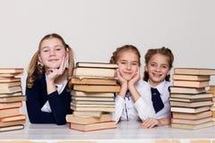 Två flickaskolflickor sitter med böcker på hans skrivbord på kursen på skola arkivbild