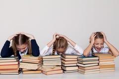 Två flickaskolflickor sitter med böcker på hans skrivbord på kursen på skola arkivfoto