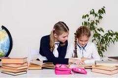 Två flickaskolflickor som sitter på hans skrivbord på kursen på skola royaltyfri bild