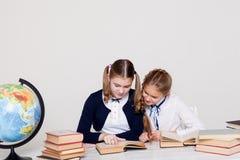 Två flickaskolflickor som sitter på hans skrivbord på kursen på skola arkivbild