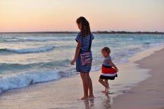 Två flickasystrar går barfota på den sandiga stranden royaltyfri bild