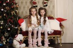 Två flickasystrar i inre jul royaltyfria bilder