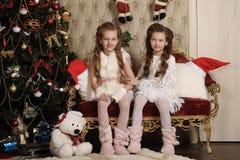 Två flickasystrar i inre jul royaltyfri foto