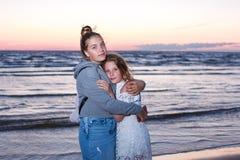 Två flickatonåringsystrar blir omfamna på seashoren arkivfoto