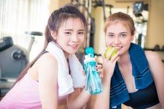 Två flickavänner dricker sötvatten och äter sund frukt i kondition Royaltyfri Fotografi
