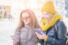 Två flickavänner i gatan i vinterkläder royaltyfria bilder