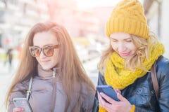 Två flickavänner i gatan i vinterkläder arkivbilder