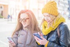 Två flickavänner i gatan i vinterkläder arkivbild