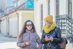 Två flickavänner i gatan i vinterkläder royaltyfria foton