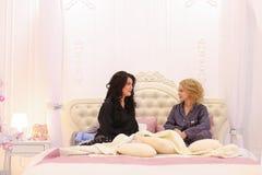 Två flickavänner pratar och skvallrar och att sitta på säng i ljus bedro Arkivfoton