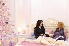 Två flickavänner pratar och skvallrar och att sitta på säng i ljus bedro Arkivbilder