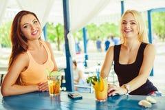 Två flickavänner som har roligt utomhus- i sommar Kvinna med exponeringsglas av coctailen på semester Arkivbilder